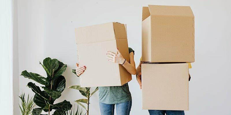 Umzugsliste - 2 Personen tragen Kisten beim Umzug
